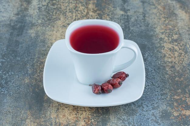 大理石の背景にローズヒップとお茶のカップ。