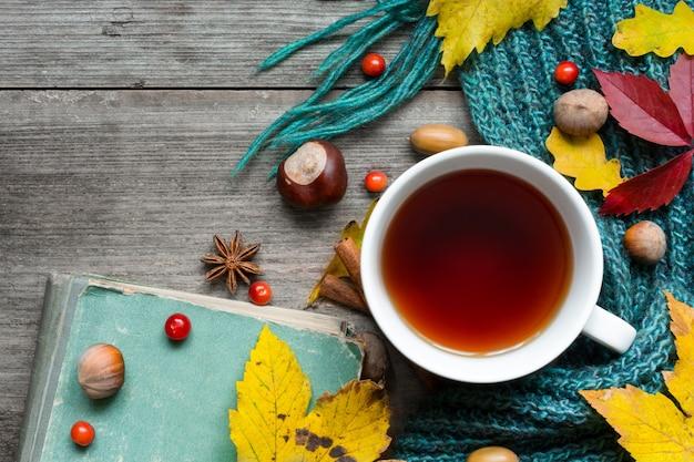 Чашка чая с шарфом и осенними листьями