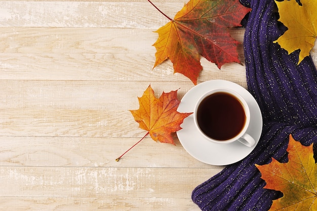 Чашка чая с шарфом и осенними кленовыми листьями - осенний натюрморт - вид сверху