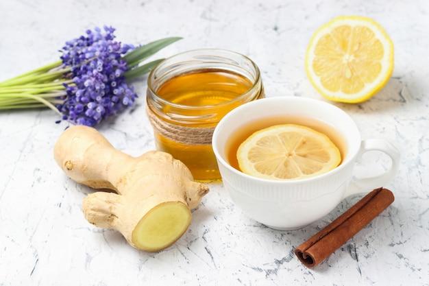 Чашка чая с нарезанным лимоном свежий корень имбиря, палочка корицы и мед с лимоном и фиалками