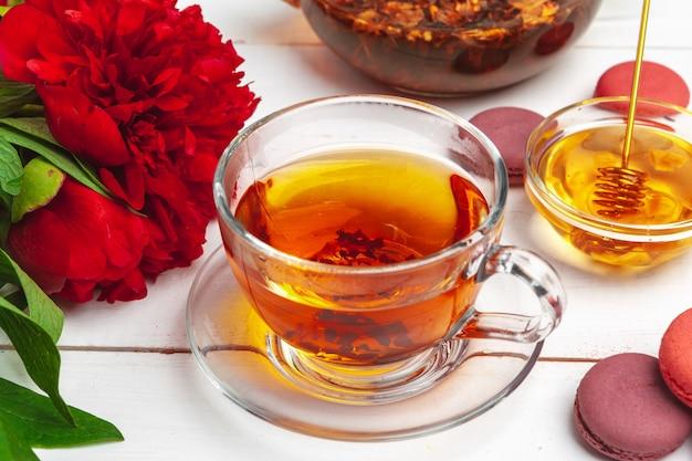 お菓子と木製のテーブルの上に花とお茶のカップ