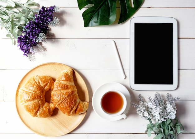 タブレット、緑の葉、花、白い木製の背景にクロワッサンと木製皿とお茶のカップ。
