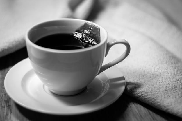 木製と綿の生地の背景にお湯に浸すティーバッグとお茶のカップ。