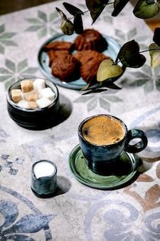 유칼립투스 가지가있는 화려한 세라믹 테이블에 우유, 설탕 큐브 및 쿠키와 함께 터키 블랙 커피 한잔. 햇빛, 그림자
