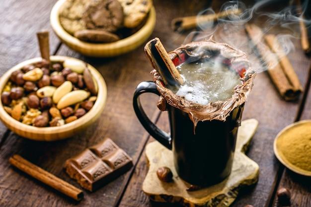 植物性ミルク、カシューナッツ、ココア、シナモン、新鮮なヘーゼルナッツで作られたビーガンホットチョコレートのカップ