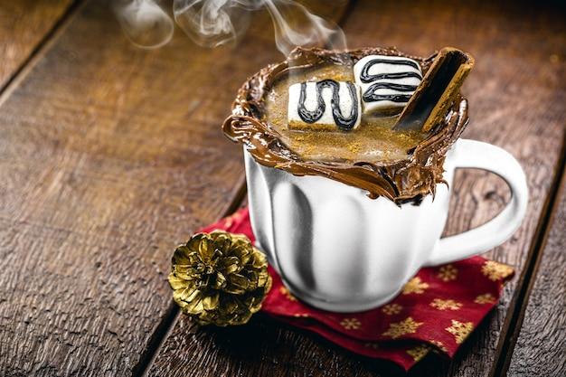 ココア、シナモン、ヘーゼルナッツ、栗で作られたビーガンホットチョコレート、蒸し、スモーキーなホットドリンクのカップ。クリスマスと新年に提供されます
