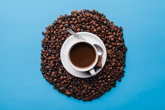 Cup on coffee beans