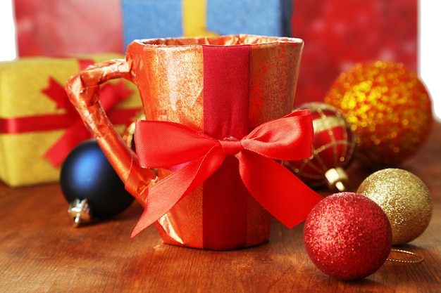 Чашка упакована в подарочную бумагу с подарками на деревянном столе на ярком фоне