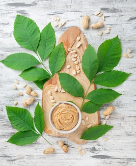 A cup of peanut butter on a wooden textured board. decorated with greens and peanuts.