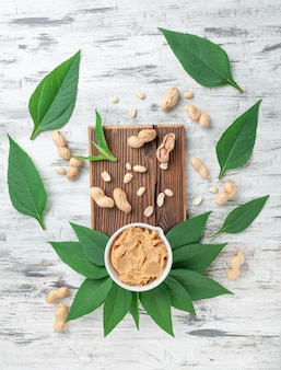 A cup of peanut butter on a wooden textured board. decorated with greens and peanuts