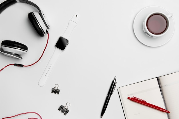 Cup, pen, and headphones on white