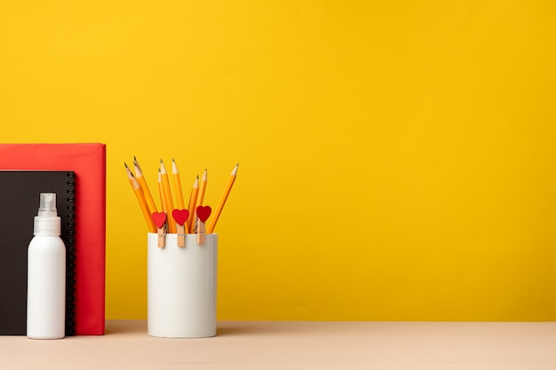 Cup of pencils and notepads on desk against yellow background, front view