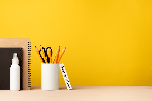Cup of pencils and notepads on desk against yellow background