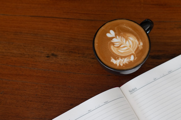 A cup of piccolo latte art  on wooden desk, relaxing time or coffee's break time during work day