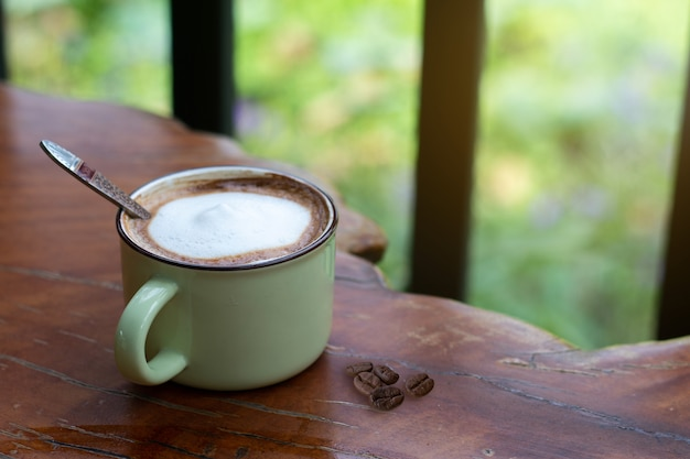 A cup of piccolo latte  on wooden desk, relaxing time or coffee's break time during work day