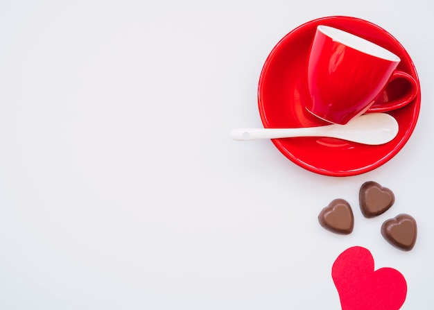 Cup on plate near chocolate sweet candies and valentine card