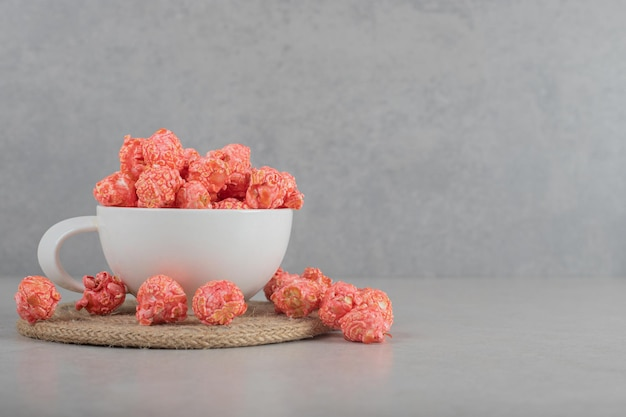 Cup of popcorn candy on a knitted trivet on marble background.
