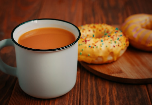 Cup of pumpkin juice and two sweet doughnuts with lemon glaze and sprinkles fresh pastries on a wooden tray white metal mug with a drink