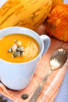 Cup of pumpkin soup with pumpkins seeds
