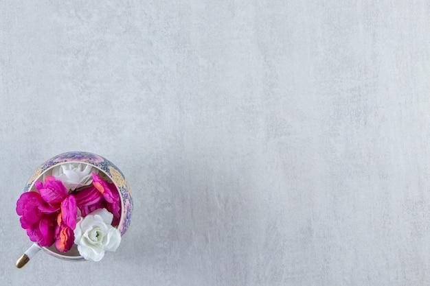 Una tazza di fiori viola e bianchi, su fondo bianco. foto di alta qualità