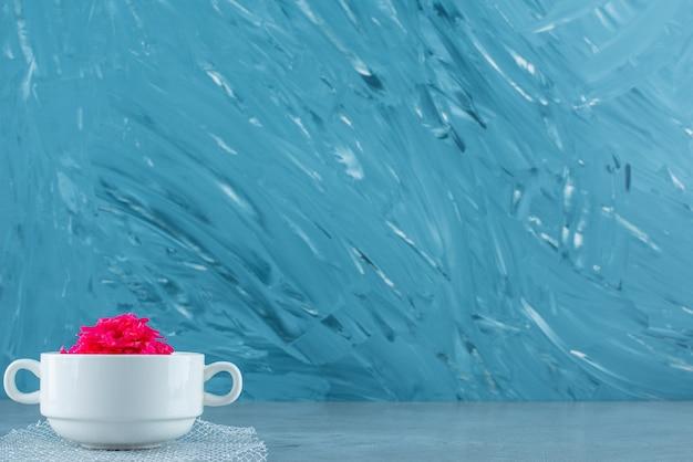 Una tazza di crauti fermentati rossi, sul tavolo blu.