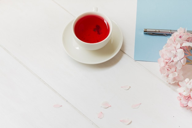 Cup of red tea next to flower