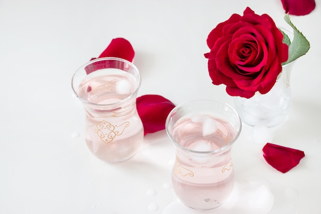 Cup refreshing rose water lemonade with ice cubes and rose flower in glass and petals on white
