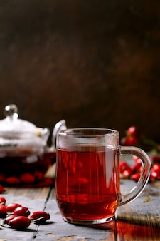 Cup of rose hip berries herbal tea and glass teapot standing on old wooden plank table with wild autumn berries around. vitamin hot beverage.