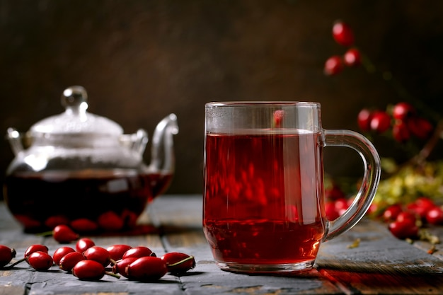 Cup of rose hip berries herbal tea and glass teapot standing on old wooden plank table with wild autumn berries around. winter hot cozy beverage.