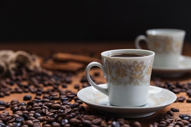 Tazza sul piattino vicino a chicchi di caffè