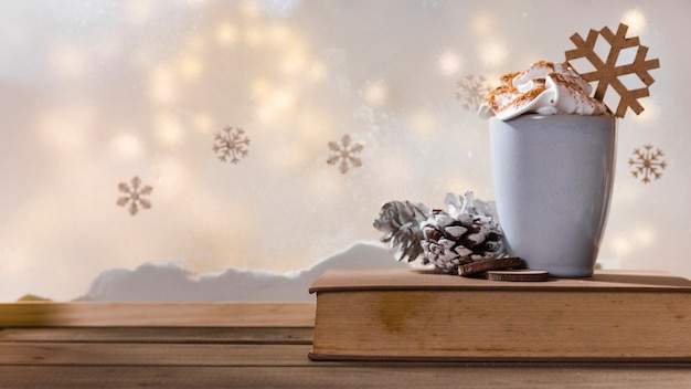 Cup, snag and book on wood table near bank of snow, snowflakes and fairy lights