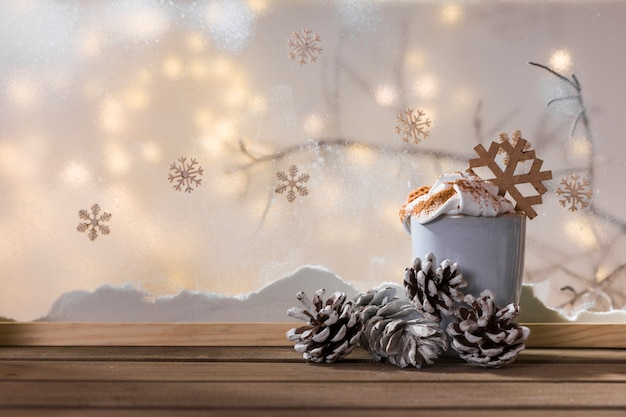 Cup and snags on wood table near bank of snow, plant twig, snowflakes and fairy lights