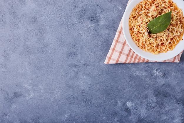 Una tazza di spaghetti con foglia di origano.