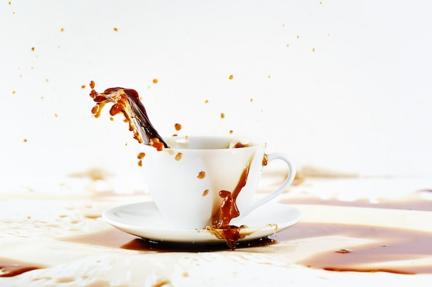 Cup of spilling coffee creating beautiful splash