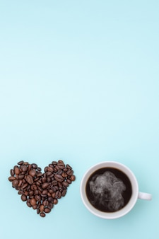 Cup of steaming hot black coffee and grains of coffee in the shape of a heart on a blue background
