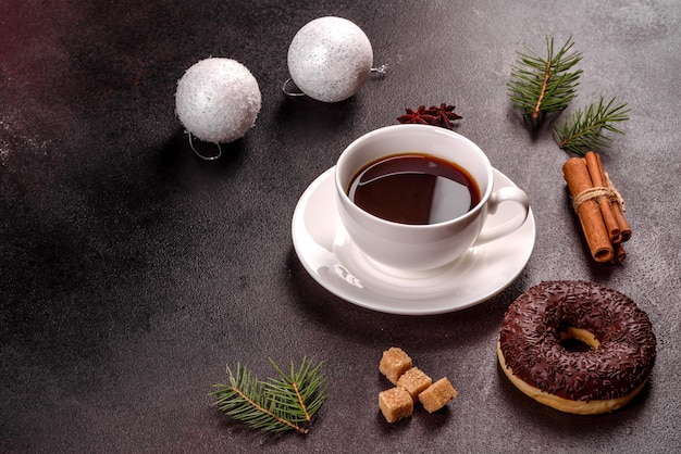 A cup of strong coffee on the christmas table with spruce twigs and toys. preparing for the holiday