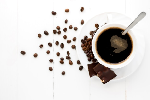 Cup of strong coffee on a white wooden surface with grains and chocolate