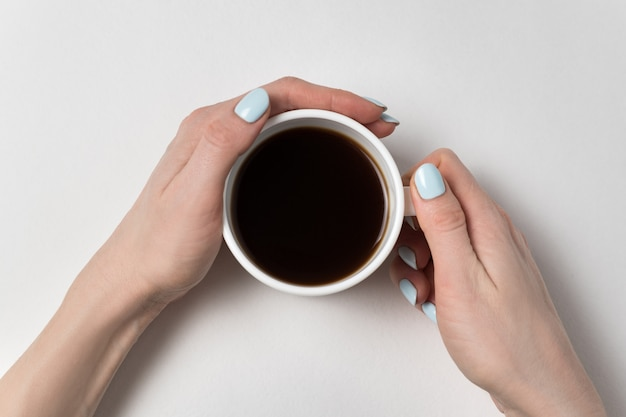 Cup of strong tea in hand on a white surface. neat manicure and a cup of coffee.