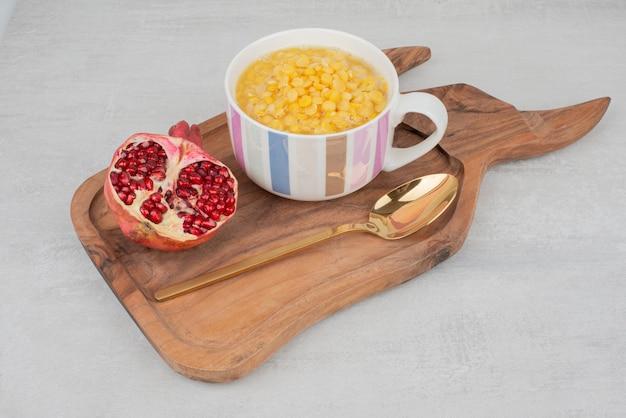 Tazza di cucchiaio di mais dolce e melograno su tavola di legno.