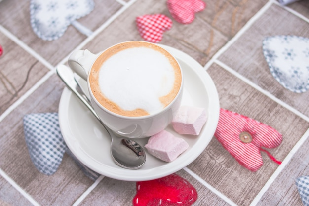 Cup of sweet morning energy drink is standing on tablecloth with a pattern in the form of hearts
