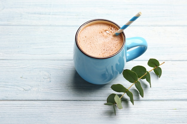 Cup of tasty cocoa drink on light wooden table