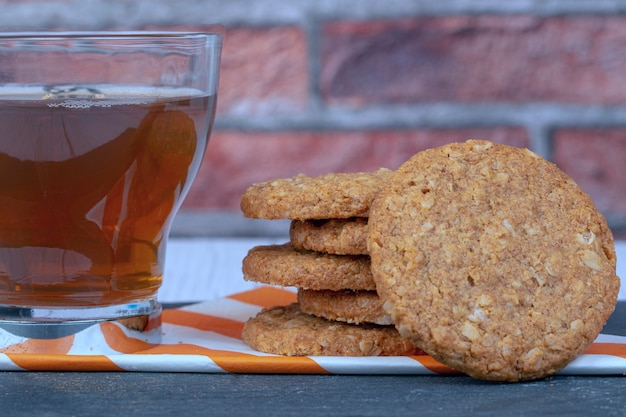 Cup of tea accompanied by oatmeal cookies on a patterned napkin on brick wall background