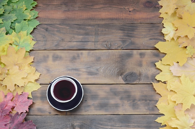 A cup of tea among a set of yellowing fallen autumn leaves on a background surface