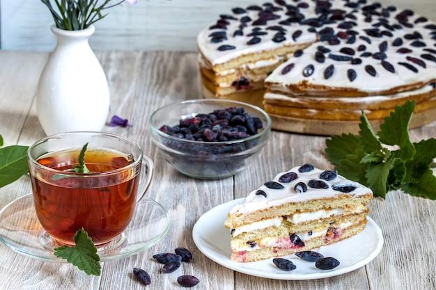 カップ茶と木製のテーブルの上のケーキ