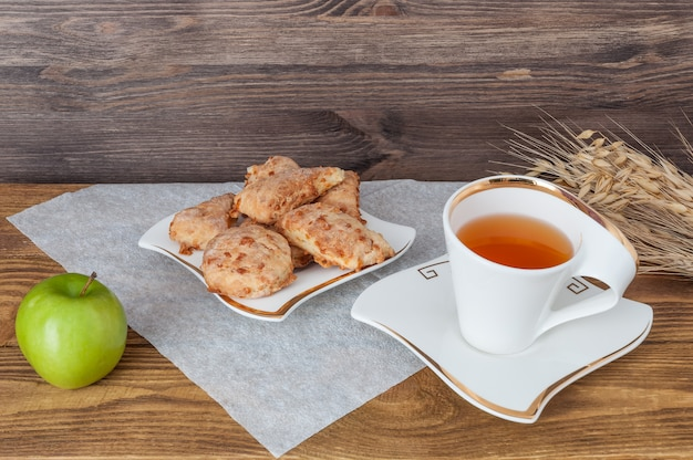 Cup of tea, apple and wheat on a wooden background