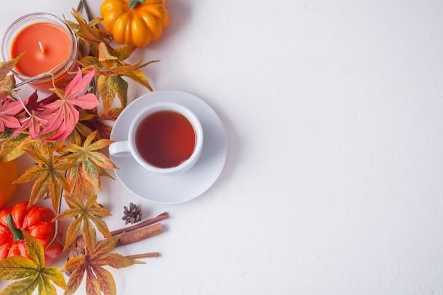 Cup of tea, autumn leaves, candle, pumpkin on white.