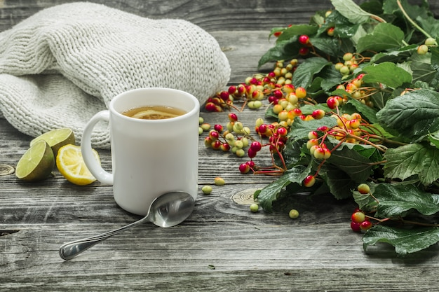 The cup of tea on a beautiful wooden background with winter sweater, berries, autumn