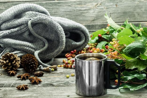 La tazza di tè su una bella parete in legno con maglione invernale, frutti di bosco, autunno