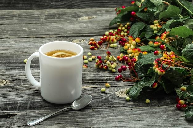 La tazza di tè su un bellissimo maglione invernale in legno, frutti di bosco, autunno