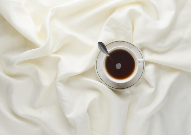 A cup of tea on the bed sheet. top view. minimalism trend.